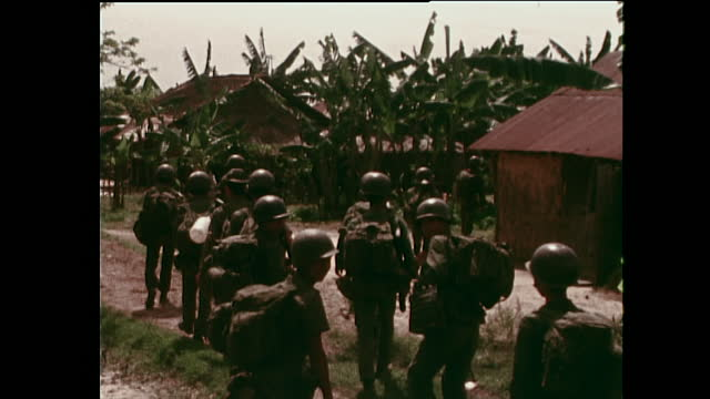 uniformed soldiers, believed to be south vietnamese army, walk into my thanh village to defend it during the vietnam war; 1972. - non us film location stock videos & royalty-free footage
