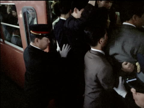 Uniformed station attendants pushing Japanese commuters into subway cars / train doors close Japanese commuters are pushed into subway cars on...