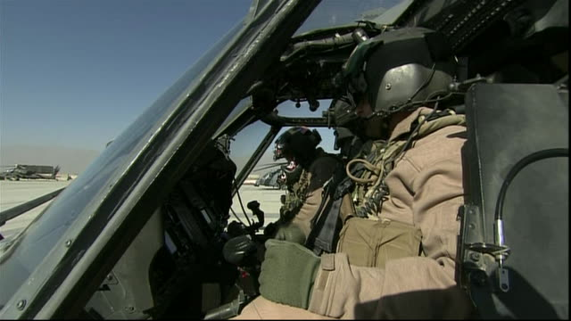uniformed us soldiers sit in pilot seat of helicopter at us army base in afghanistan. - afghan national army stock videos & royalty-free footage