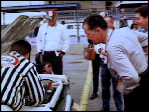 ws union 76 flag flying / ws 1967 amc rambler american 220 driving by on daytona speedway pit track / same as previous shot / ws rambler turning... - circuito di daytona video stock e b–roll