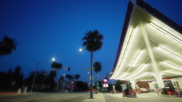 T/L WS LA Union 76 gas station built in Streamline Moderne style and traffic on highway, dusk to night, Beverly Hills, California, USA