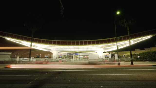 T/L WS Union 76 gas station built in Streamline Moderne style at night, traffic in foreground, Beverly Hills, California, USA