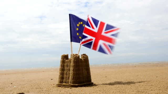 stockvideo's en b-roll-footage met union and eu flags in sandcastle - brexit