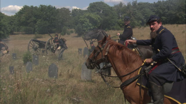 union army soldiers take cover behind gravestones during a civil war battle. - gettysburg stock-videos und b-roll-filmmaterial