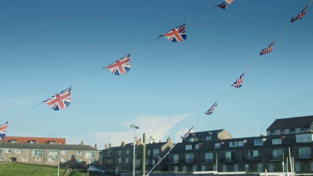 vídeos de stock e filmes b-roll de union jack bunting flapping in breeze - cultura britânica