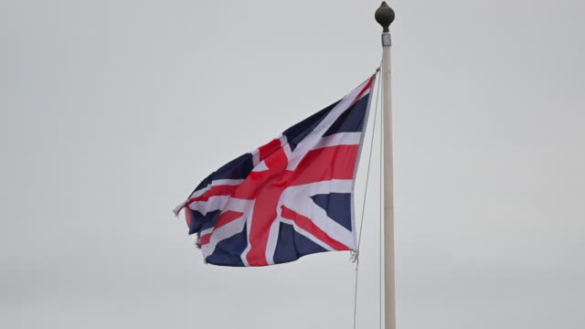 union jack flag blows in the wind at the ford engine plant on january 12, 2019 in bridgend, wales. ford has announced a shake-up of its european... - bandiera del regno unito video stock e b–roll