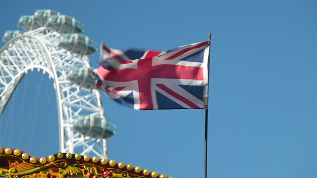 Union Jack flag blows in the wind with London Eye in background.
