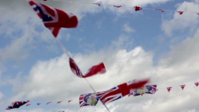 uk union jack flag bunting on summer sky during a street party - bandiera del regno unito video stock e b–roll
