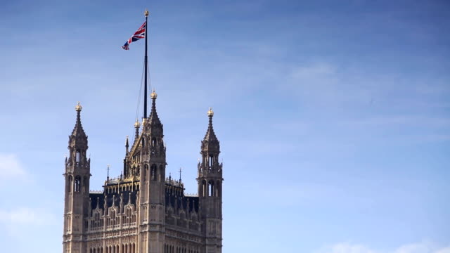 A union jack flag flying on the Victoria Tower, Houses of Parliament, London.
