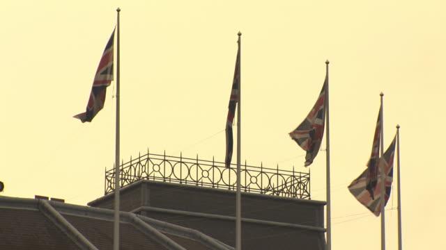vídeos de stock e filmes b-roll de union jack flags flap in a breeze at dusk on trafalgar square's grand building, london, uk. - quatro objetos
