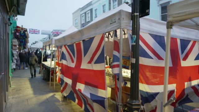 stockvideo's en b-roll-footage met union jack vlaggen op een marktkraam in portobello road, londen - rommelmarkt