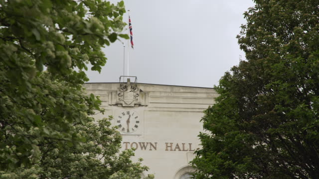 vidéos et rushes de union jack flies above facade of a british town hall - hackney