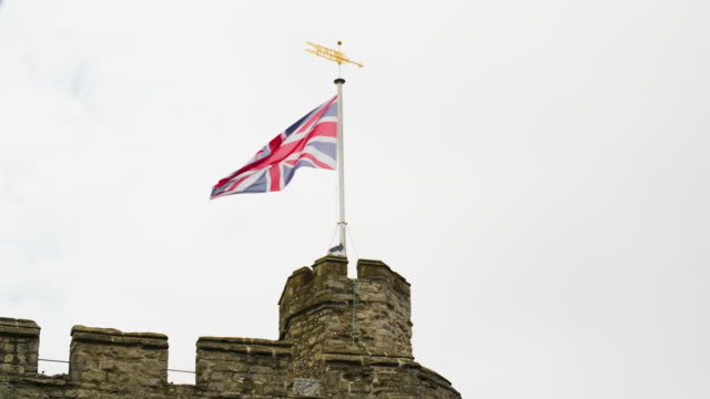 a union jack flies under a weather vane on canterbury's westgate, uk. - カンタベリー点の映像素材/bロール