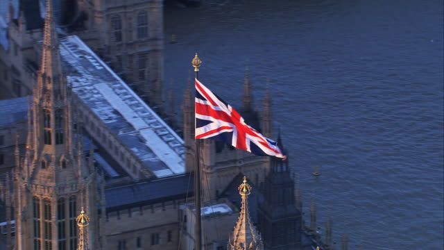 vídeos de stock e filmes b-roll de union jack voar sobre as casas do parlamento - política