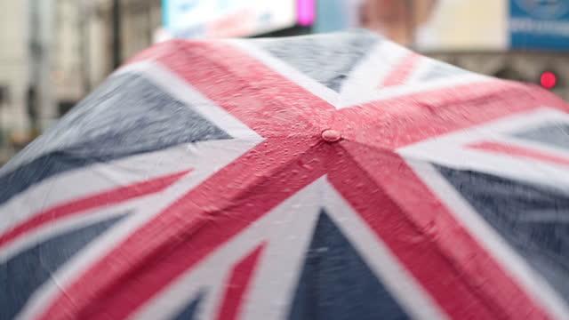 A Union Jack umbrella spins in the rain on a London sidewalk.