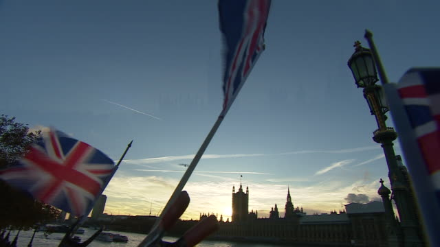 Union Jacks flying outside the Houses of Parliament at Sunset
