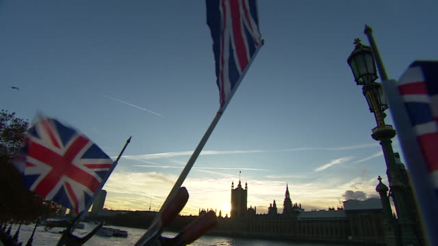 vídeos de stock e filmes b-roll de union jacks waving outside the houses of parliament - bandeira da grã bretanha