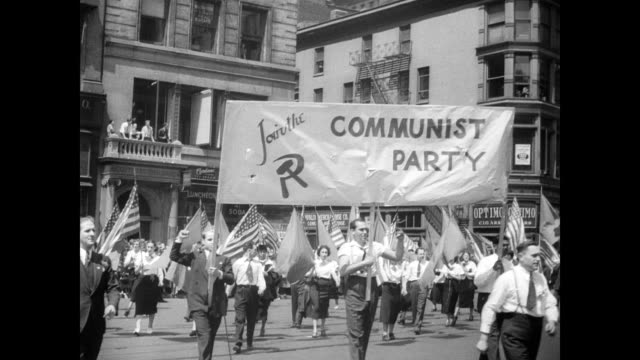 / union members and communists have parade in new york to commemorate may day / aerial of large crowd / communist party banner leads parade full of... - comunismo video stock e b–roll