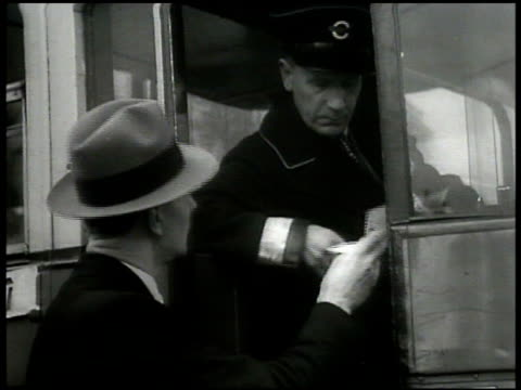vídeos de stock e filmes b-roll de union members giving two middleaged women ballots giving ballot to streetcar conductor to old man at door int vs worker voting on ballot woman at... - 1935