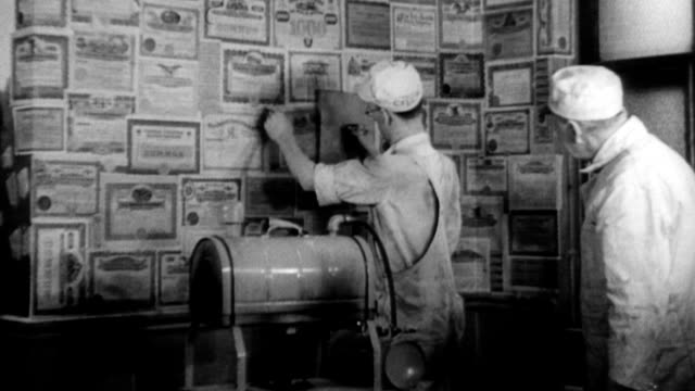 Union members laughing and standing in front of a wall filled with bond certificates from the Great Depression / workers steam bonds and pull...