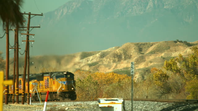 A Union Pacific freight train with three locomotives speeds through the California desert.