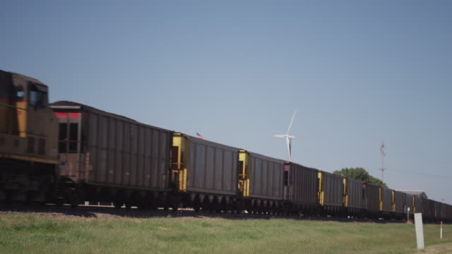Union Pacific railroad engine and train roll by small wind powered turbine in industrial park.