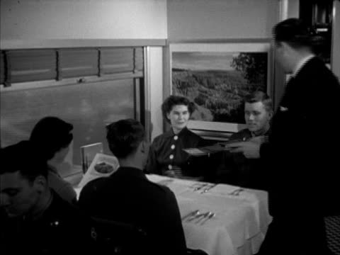 Union Pacific Railroad locomotive passenger cars passing by INT couples at dining table in diner car getting menus from waiter chef Frank Daniels...