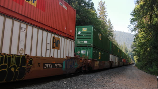 union pacific train carries freight on tracks running along i-5 at soda creek road in dunsmuir, california, while the hirz fire burns nearby, august... - 貨物列車点の映像素材/bロール