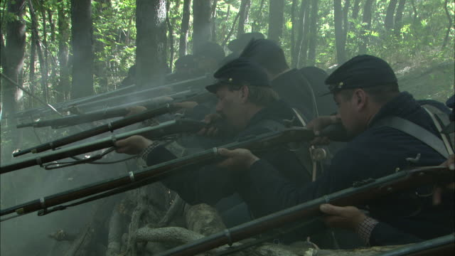 union riflemen fire from the cover of interlaced branches during the civil war. - gewehr stock-videos und b-roll-filmmaterial