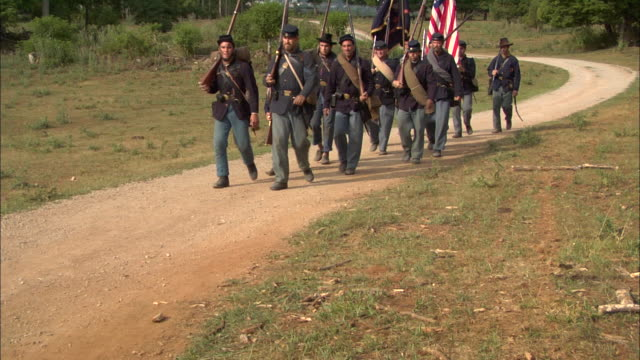 union soldiers carry the union flag as they march along a dirt road. - gettysburg stock-videos und b-roll-filmmaterial