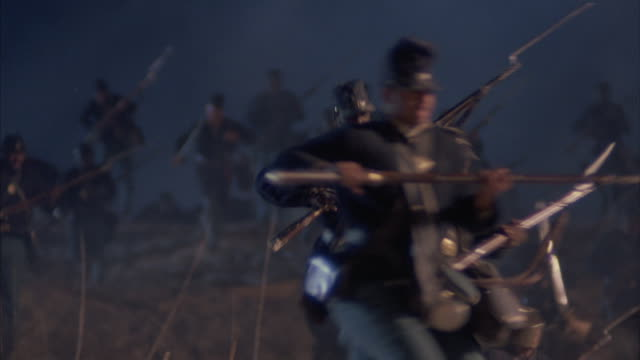 union soldiers charge the enemy carrying american flags and rifles. - gewehr stock-videos und b-roll-filmmaterial
