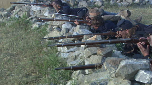 union soldiers fire rifles from behind a rock wall in a civil war reenactment. - gewehr stock-videos und b-roll-filmmaterial
