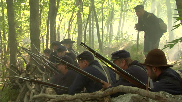 union soldiers take cover in a forest and fire their rifles during a civil war battle. - gewehr stock-videos und b-roll-filmmaterial