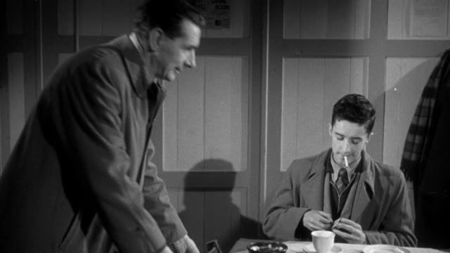 1955 MONTAGE Union worker buying coffee in cafe and explaining union organization to a new member / United Kingdom