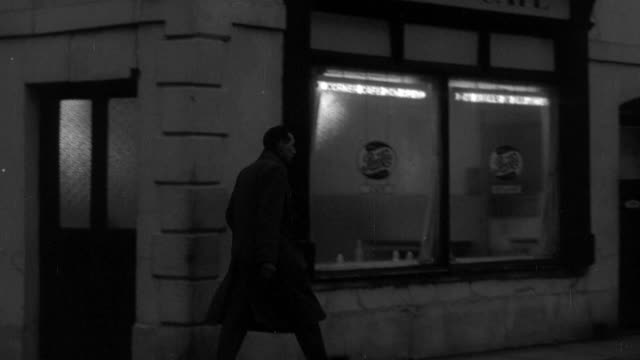 1955 MONTAGE Union worker walking into a cafeÈ for a meeting / United Kingdom