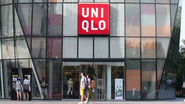 A Uniqlo logo is displayed on a shopping bag outside a Uniqlo store in Beijing The Uniqlo logo is displayed on a glass door entrance to the store in...