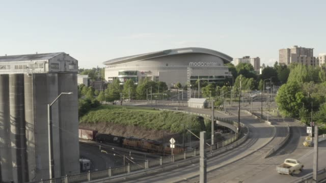 a unique aerial view of a sports arena with a train passing shot in 4k. portland. oregon. usa. - portland oregon stock videos & royalty-free footage
