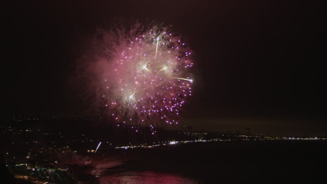 a unique pattern of fireworks bursts over santa monica bay, with santa monica city lights in the background. - santa monica stock videos & royalty-free footage