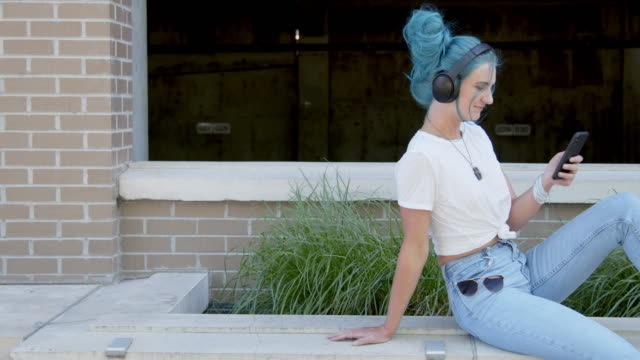 unique, spunky, fashionable young millennial woman listening to wireless bluetooth headphones and scrolling social media or playlist music or podcasts outdoors in the summer - hair bun stock videos & royalty-free footage