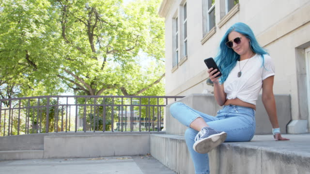 unique spunky fashionable young woman with fun cute teal blue green dyed hair using her mobile cell smartphone to text friends, check her email, check her bank account balance, and stay connected while on the go outdoors in the summer - text stock videos & royalty-free footage