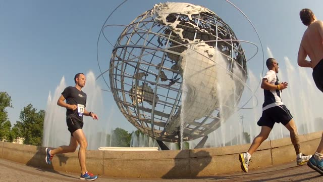 unisphere with magestic fountains shoot water in air with runners in foreground - unisphere stock videos & royalty-free footage