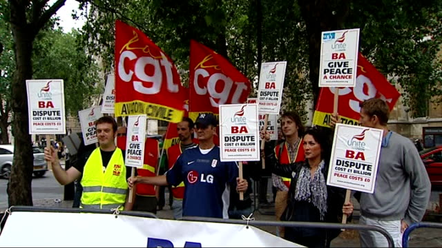 unite union members protest at british airways's agm; unite union members holding placards / various of protesters holding placards behind 'ba give... - 年次総会点の映像素材/bロール