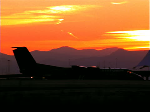 stockvideo's en b-roll-footage met pan silhouette united airlines airplane taxiing on runway past airport at sunset / denver - dia