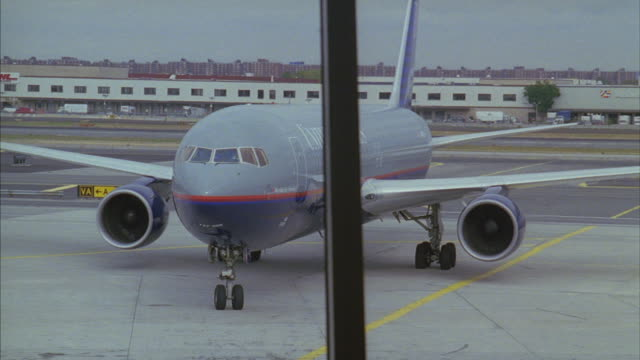 A United Airlines Airplane taxiing to gate at airport terminal.