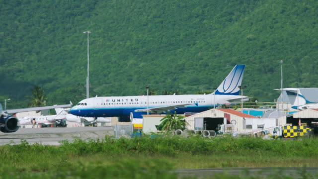 ws pan united airlines and jetblue plane taxiing in airport / st. maarten - taxiway stock-videos und b-roll-filmmaterial