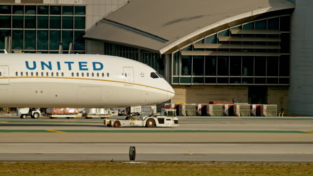 ws pan united airlines boeing 787 dreamliner is towed across tarmac by tow tractor vehicle near bradley terminal at lax - control stock videos & royalty-free footage
