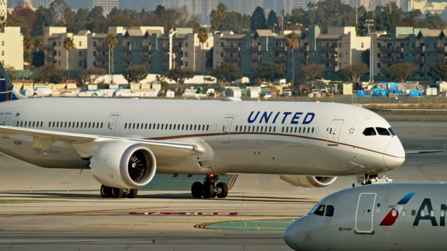 vidéos et rushes de ws pan united airlines boeing 787 dreamliner is towed across tarmac by tug as american airlines airbus 321 crosses in foreground - avion de tourisme