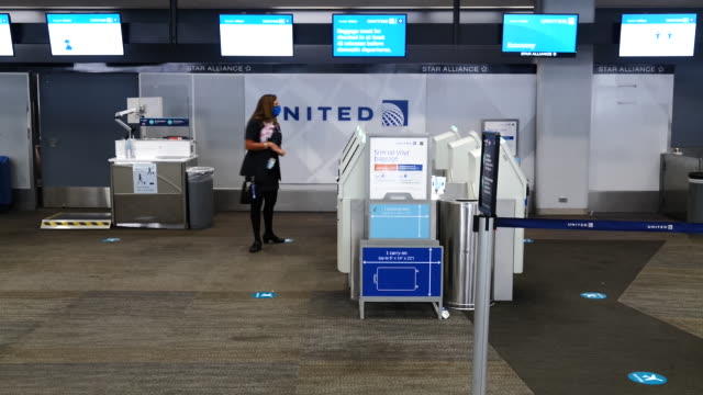 united airlines employee helping woman at self-service check-in kiosk at san francisco international airport in san francisco, california, u.s., on... - san francisco international airport stock videos & royalty-free footage