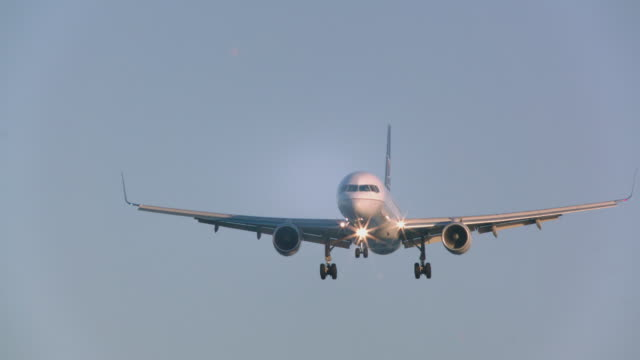 vidéos et rushes de united airlines jet plane approaches runway prior to landing in late-afternoon light - s'approcher
