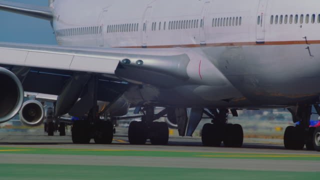 United Airlines jumbo 747 turns on taxi to runway, tilt from fuselage to landing gear with waiting airplanes stacked in background